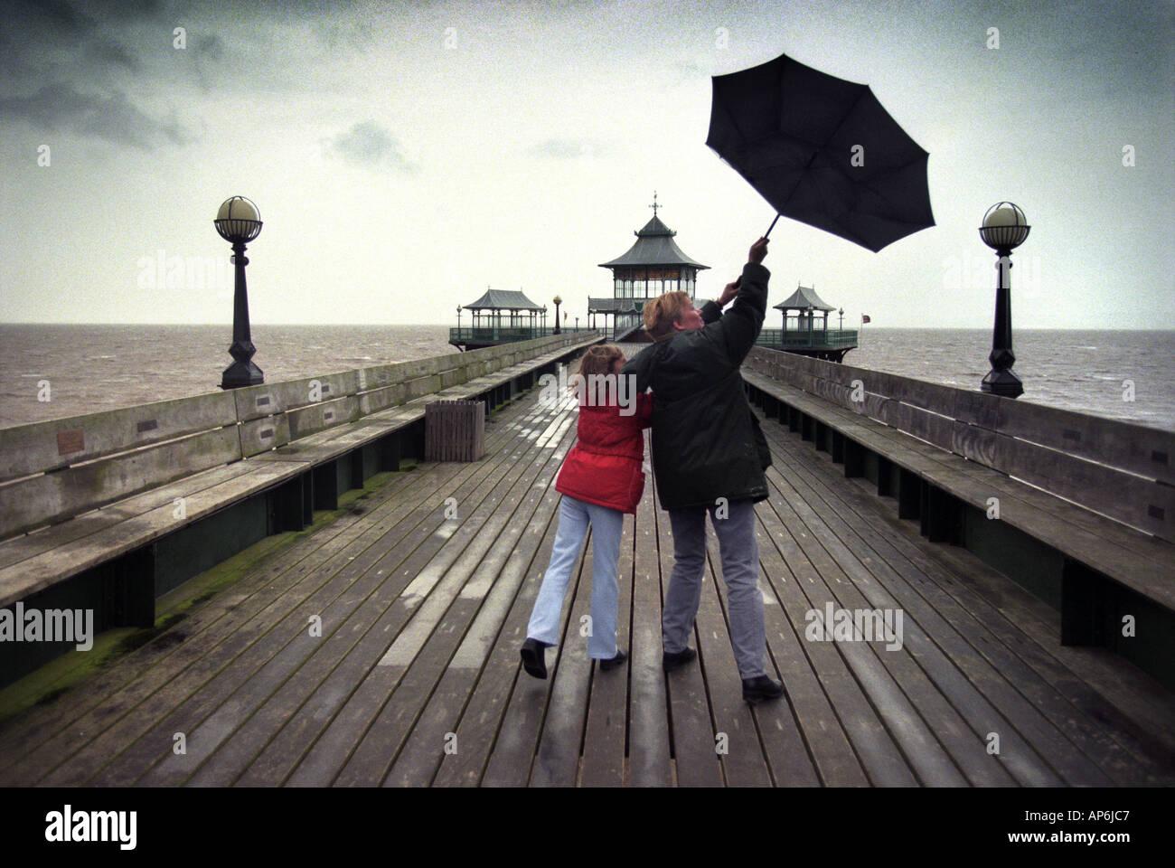 Una ragazza e sua madre in lotta con un ombrello nero durante una passeggiata sul molo di CLEVEDON NORTH SOMERSET Foto Stock