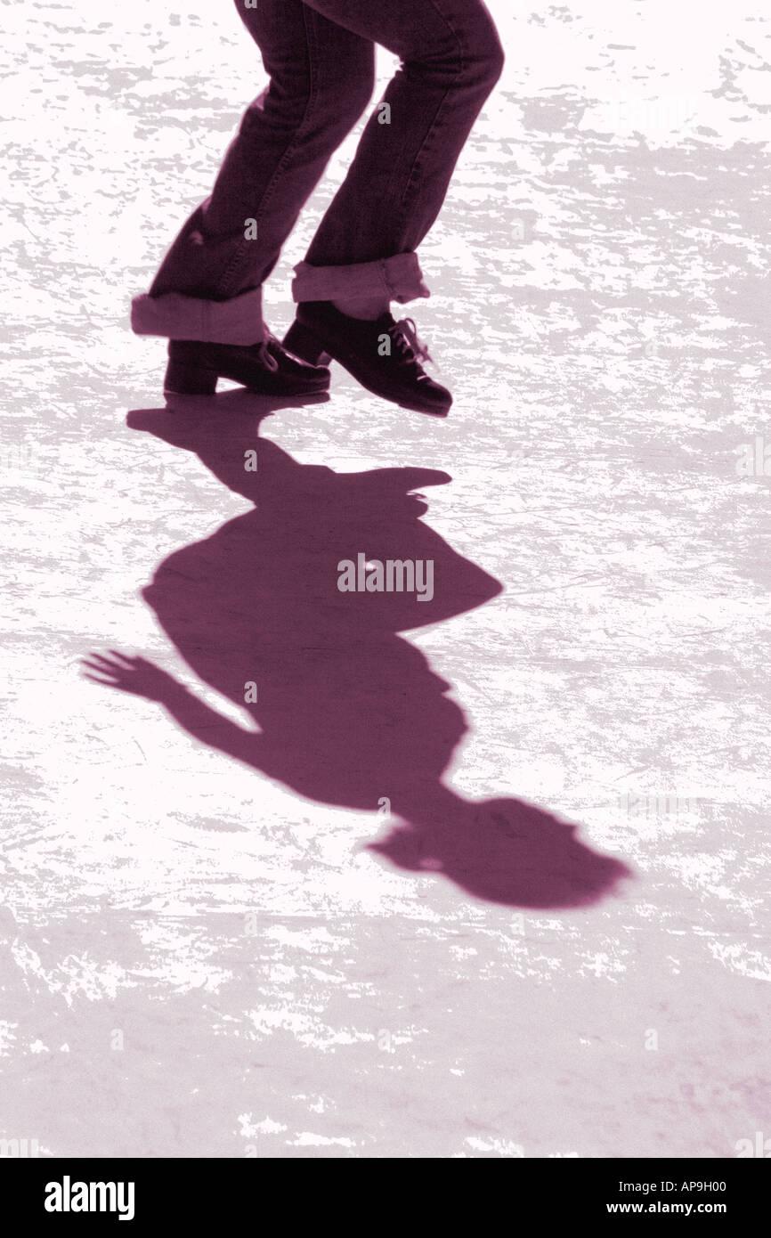 Un singolo tocco ballerino e il suo o la sua ombra balli in un contesto urbano Immagini Stock
