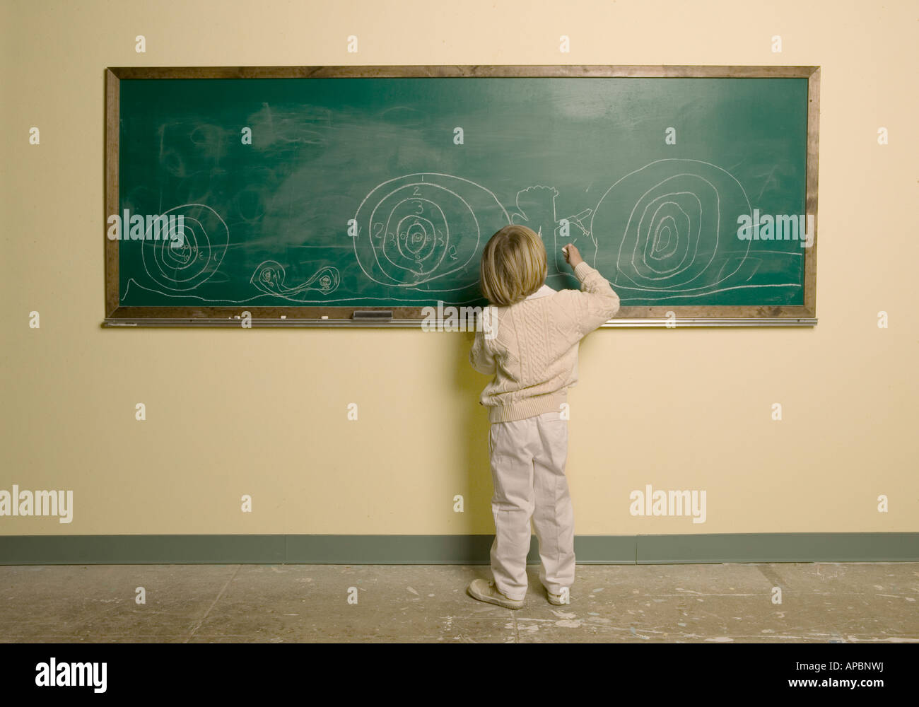 Ragazzo giovane scrive con il gesso sulla grande orizzontale chalk board idee pensare la creazione di learning progettazione Foto Stock