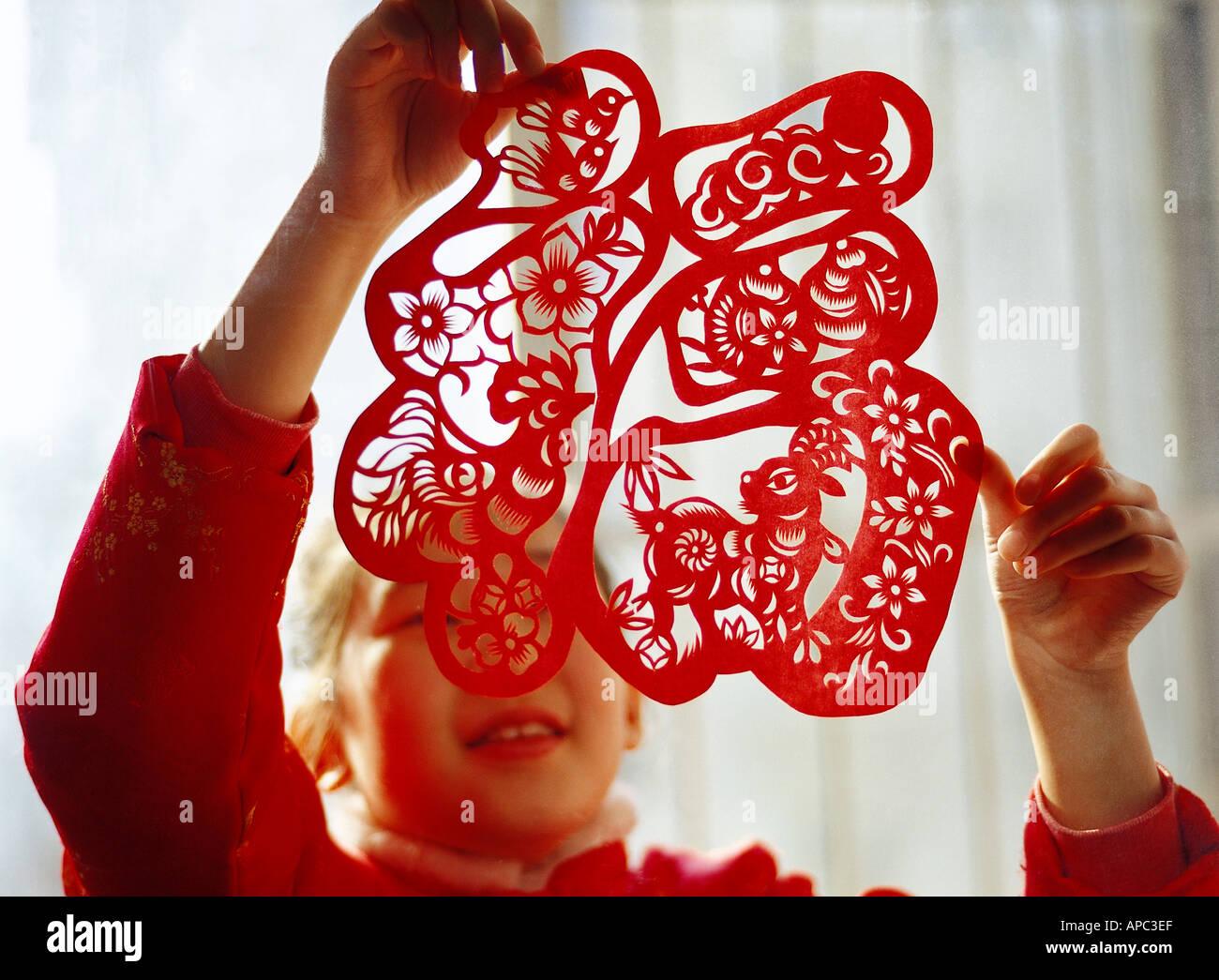 Un Cinese 9 10 anno vecchia ragazza incollando una finestra carta tagliata sul cinese capodanno Foto Stock