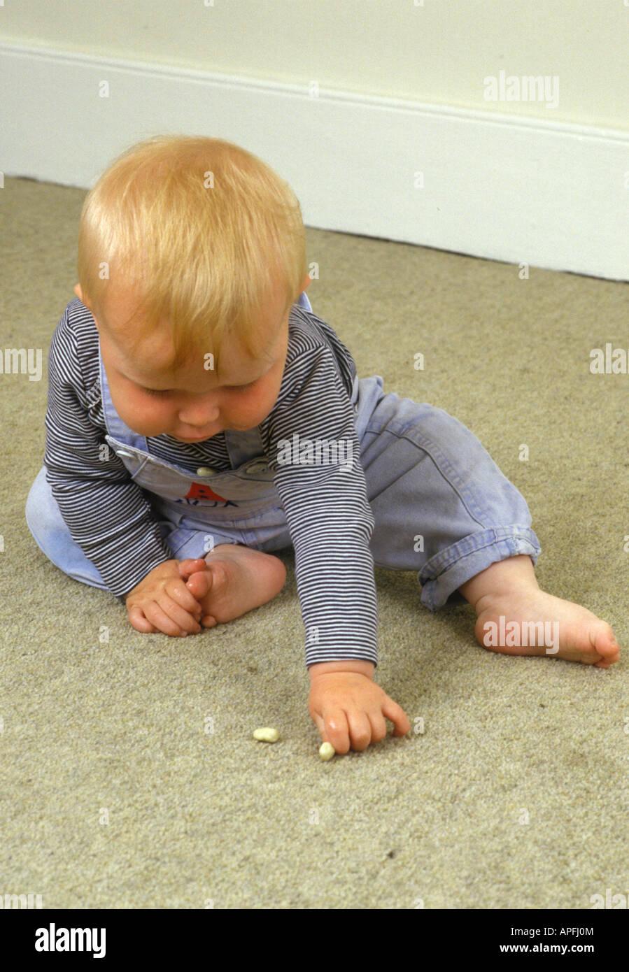 Baby il prelievo di oggetto sul tappeto Immagini Stock