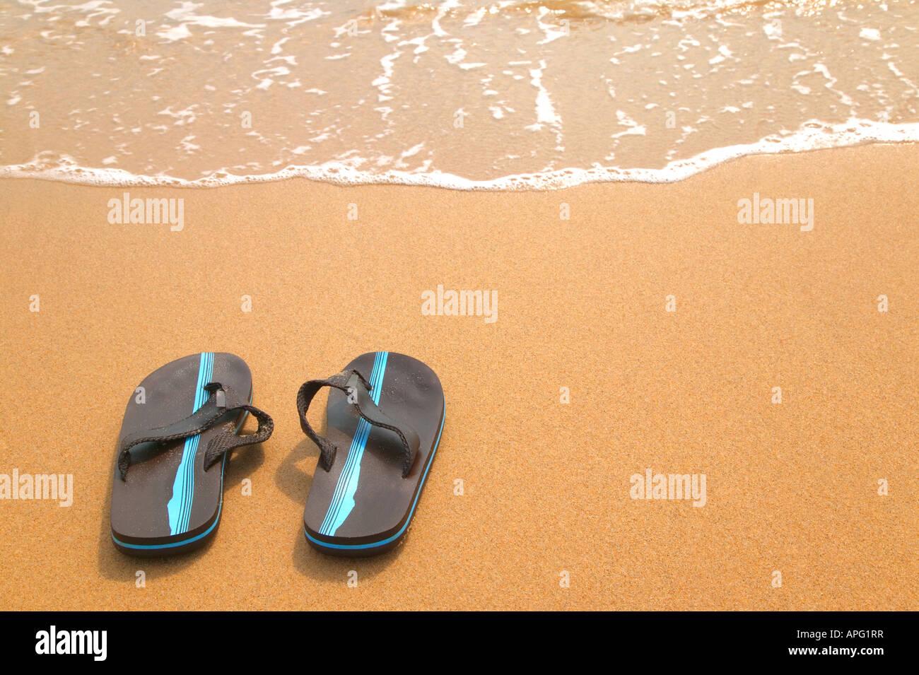 Una coppia di flip flop su una spiaggia di sabbia fine e dorata dal bordo delle acque Immagini Stock