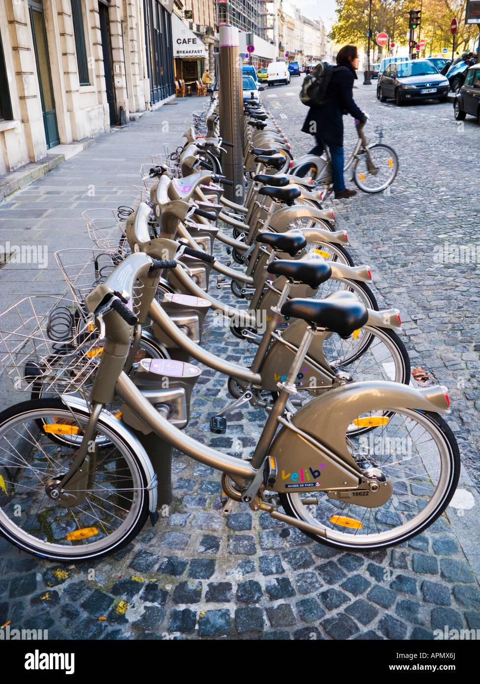 Ciclista gite fuori da un ciclo di Velib rack con le biciclette a noleggio a Parigi, Francia Immagini Stock