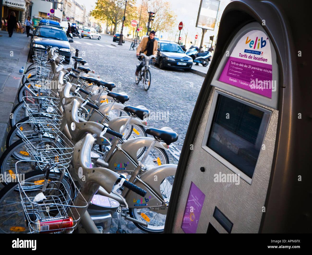 L'uomo ciclista su un assunto Velib corse in bicicletta verso il ciclo di rack e di pagare dalla stazione di Immagini Stock