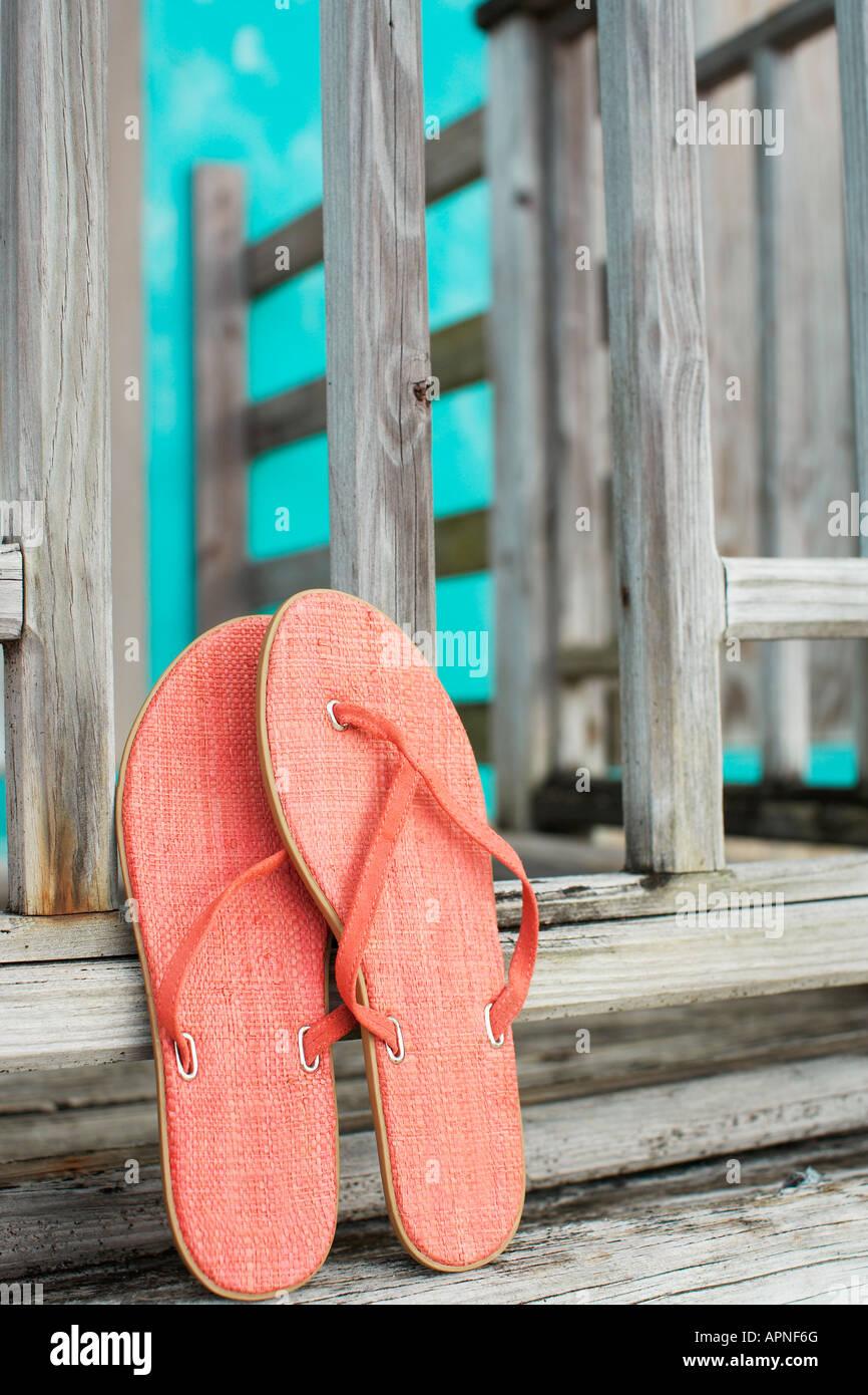 Rosa flip flop appoggiata sulla recinzione Foto Stock