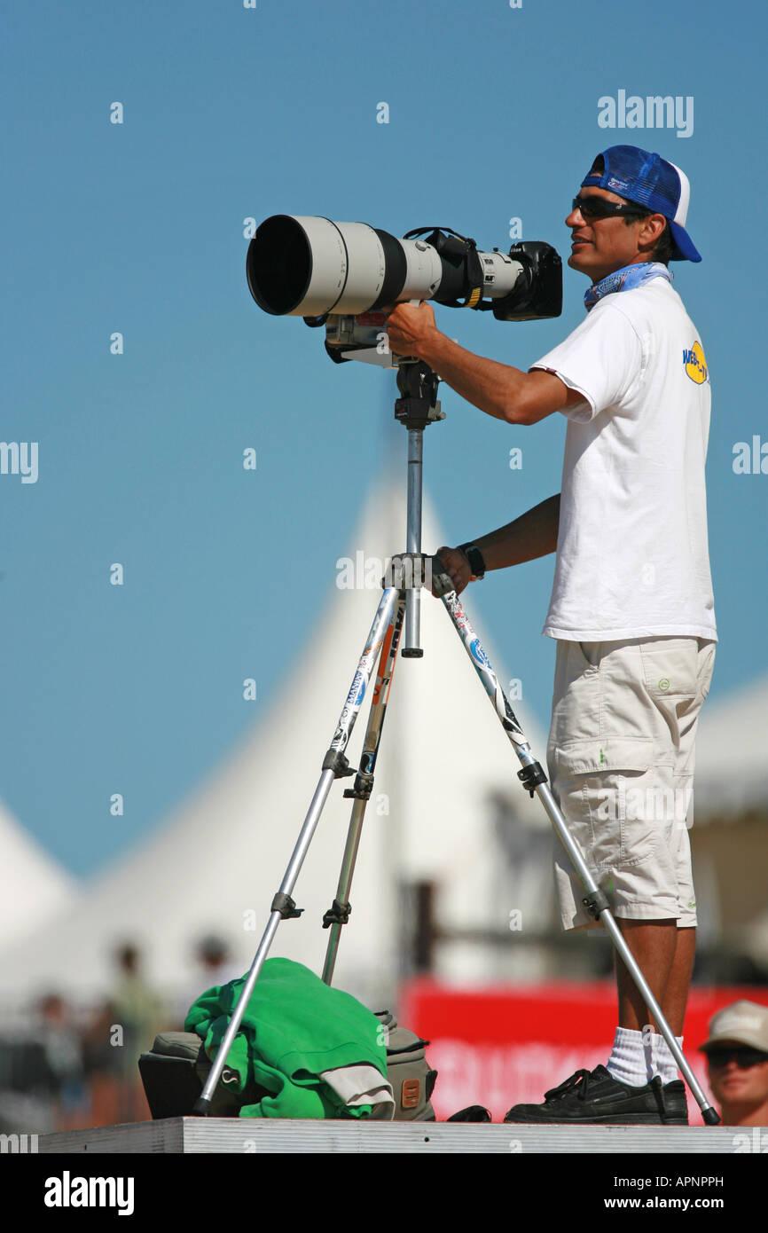 Un fotografo utilizzando un super teleobiettivo. Immagini Stock