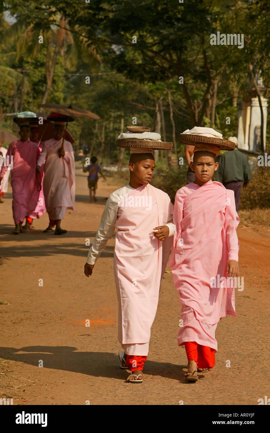 Le monache a piedi in una linea di raccogliere elemosine, Bago, Nonnen in rosa Roben, gehen in Reihe, Almosen sammeln, bekommen ungekochten Reis, Moe Immagini Stock
