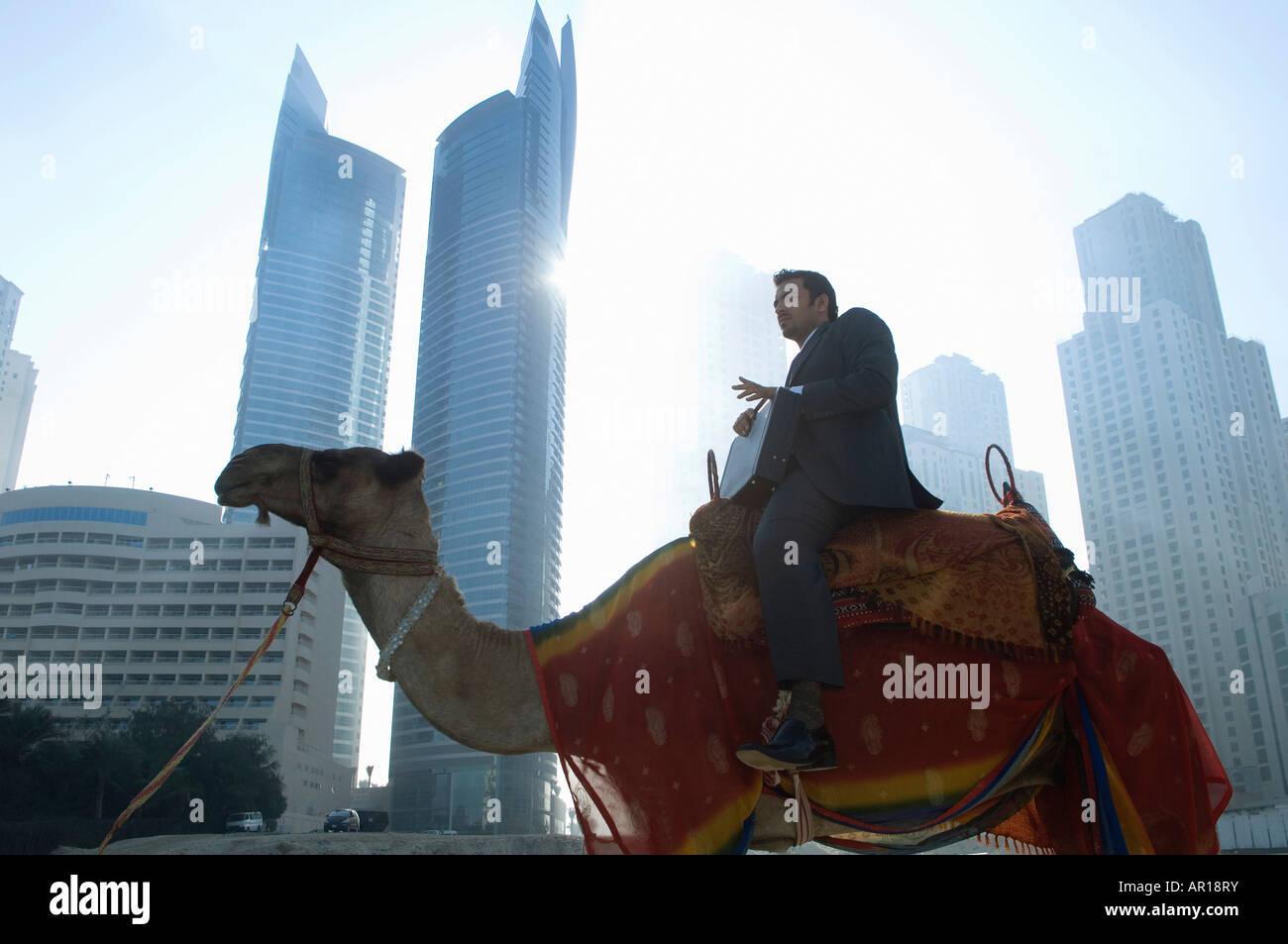 Imprenditore seduto sul cammello, torri visto attraverso la nebbia in background Immagini Stock