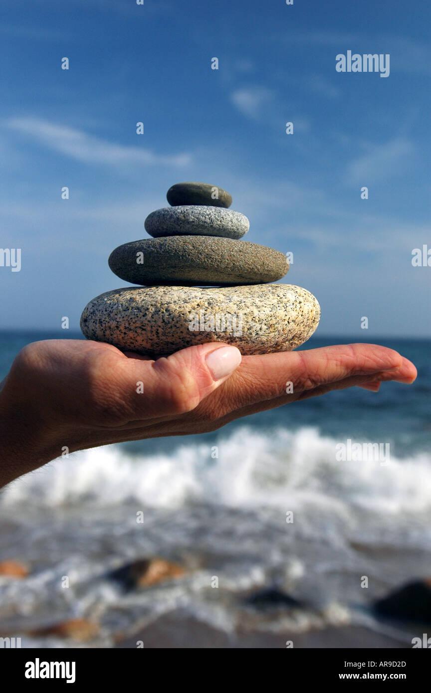 Mano con pila di rocce design e finiture sereno Immagini Stock