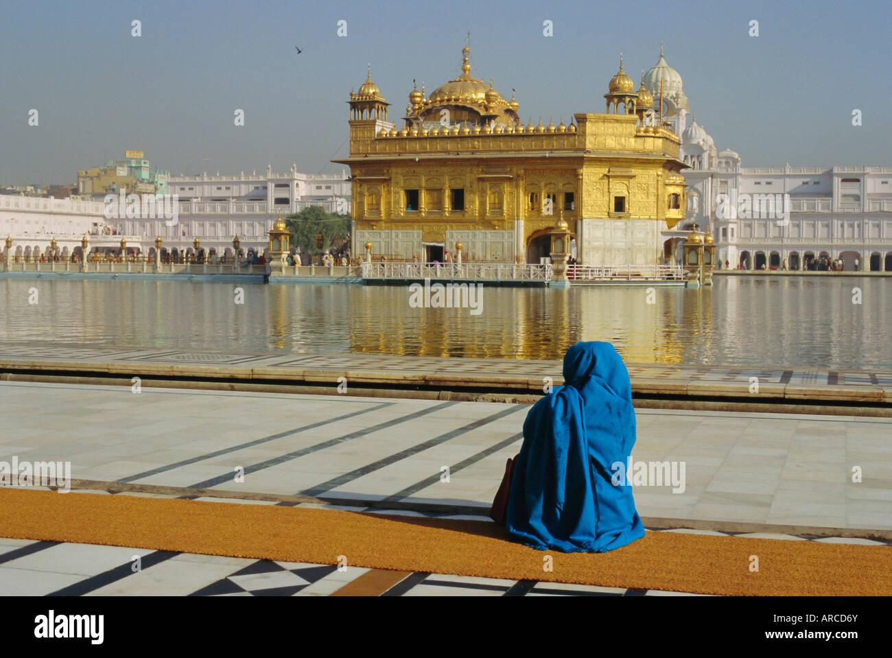 Un pellegrino in blu si siede dal Santo Pool di Nectar presso il Tempio d'oro, il centro della religione Sikh, Immagini Stock