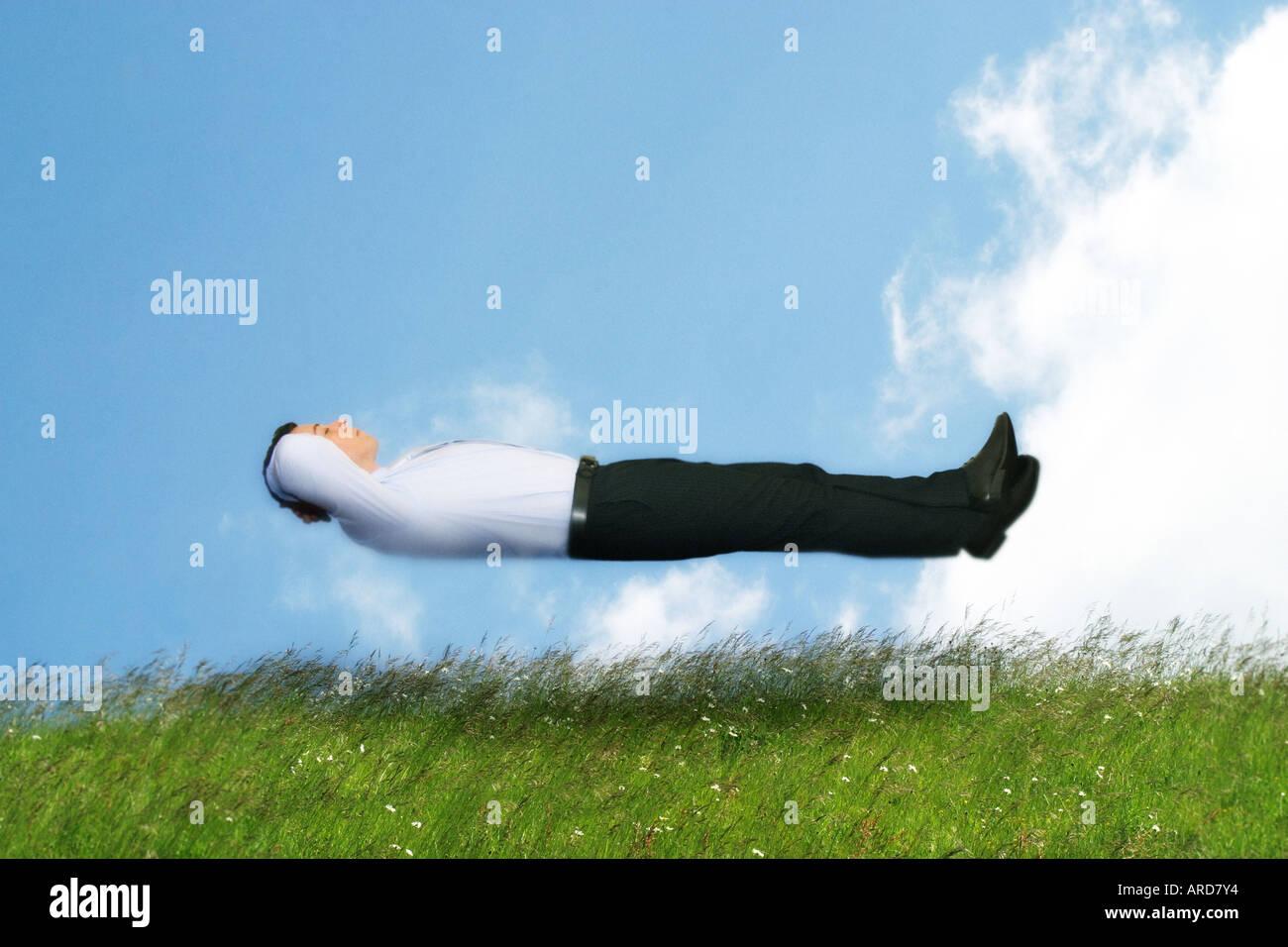 Uomo in camicia e cravatta galleggianti in aria Immagini Stock