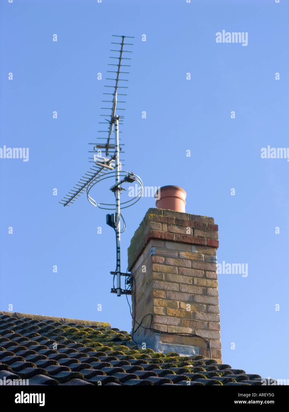 Immagine a colori alla ricerca fino a un tetto e chimley che ha un'antenna tv collegato ad esso, cielo blu chiaro Foto Stock
