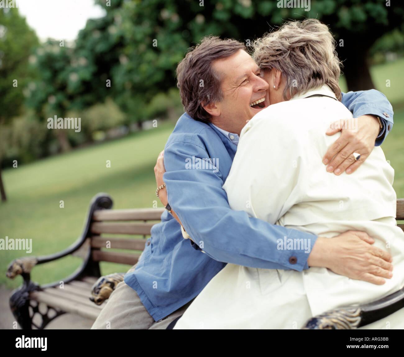 Medioevo giovane ridendo e abbracciando su una panchina nel parco Immagini Stock