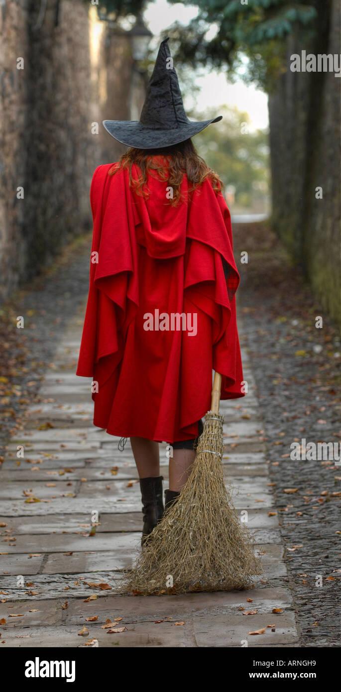Vista posteriore di una giovane donna che indossa un mantello rosso e una strega hat trascinando una scopa a camminare in un vicolo solitario Immagini Stock