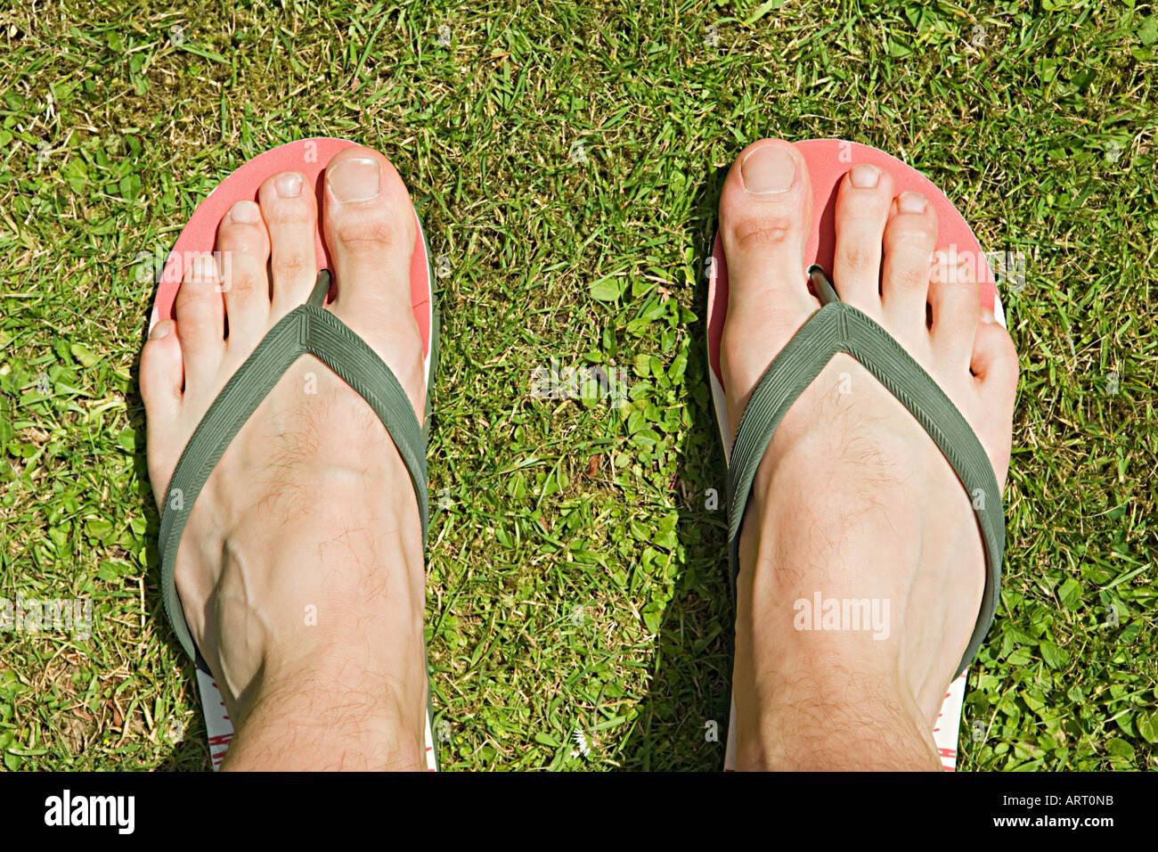 I piedi di un uomo in flip flop Immagini Stock