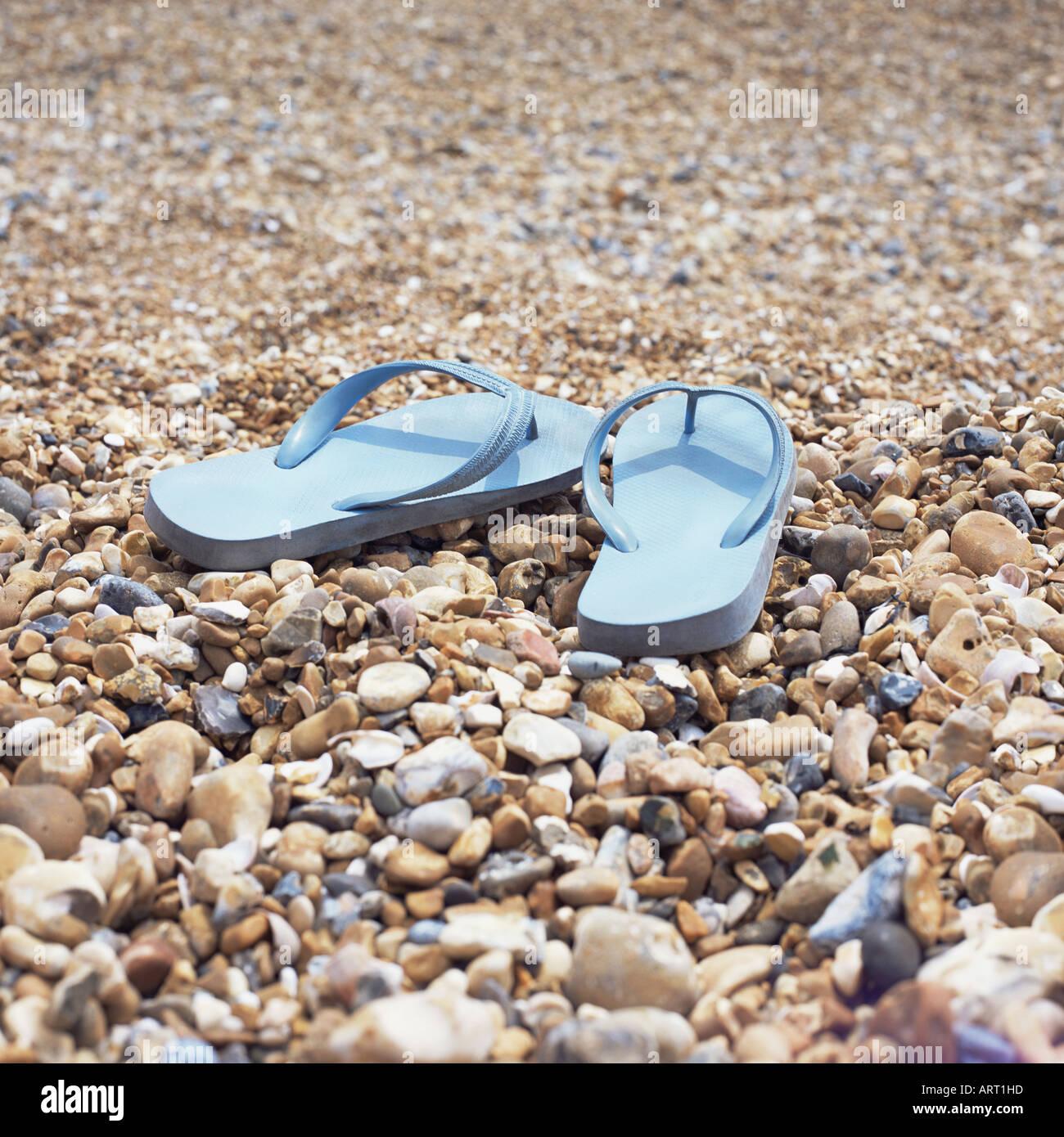 Il flip flop su una spiaggia di ciottoli Immagini Stock