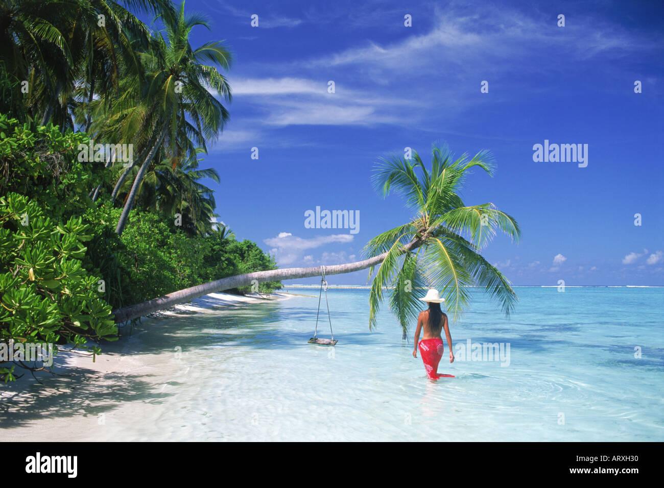 Donna che indossa red sarong e white hat camminando lungo la spiaggia con sovrastante Palm tree in Maldive Immagini Stock