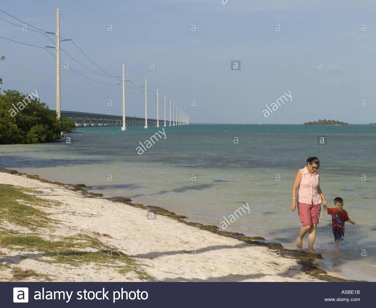La madre e il bambino a piedi lungo la spiaggia con sullo sfondo il 7 miles bridge Florida Keys Immagini Stock