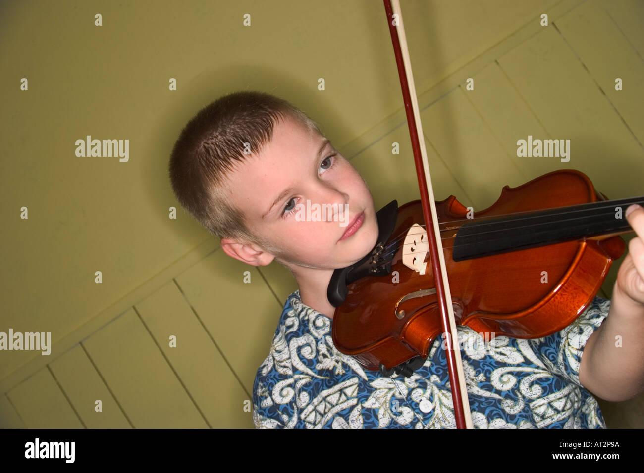 Giovane ragazzo in pratica il suo violino Immagini Stock