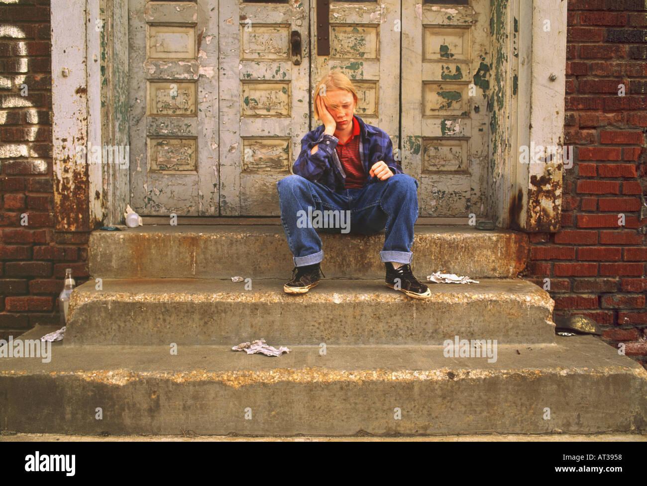 Triste runaway ragazzo seduto sui gradini di un abbandonato edificio urbano Immagini Stock