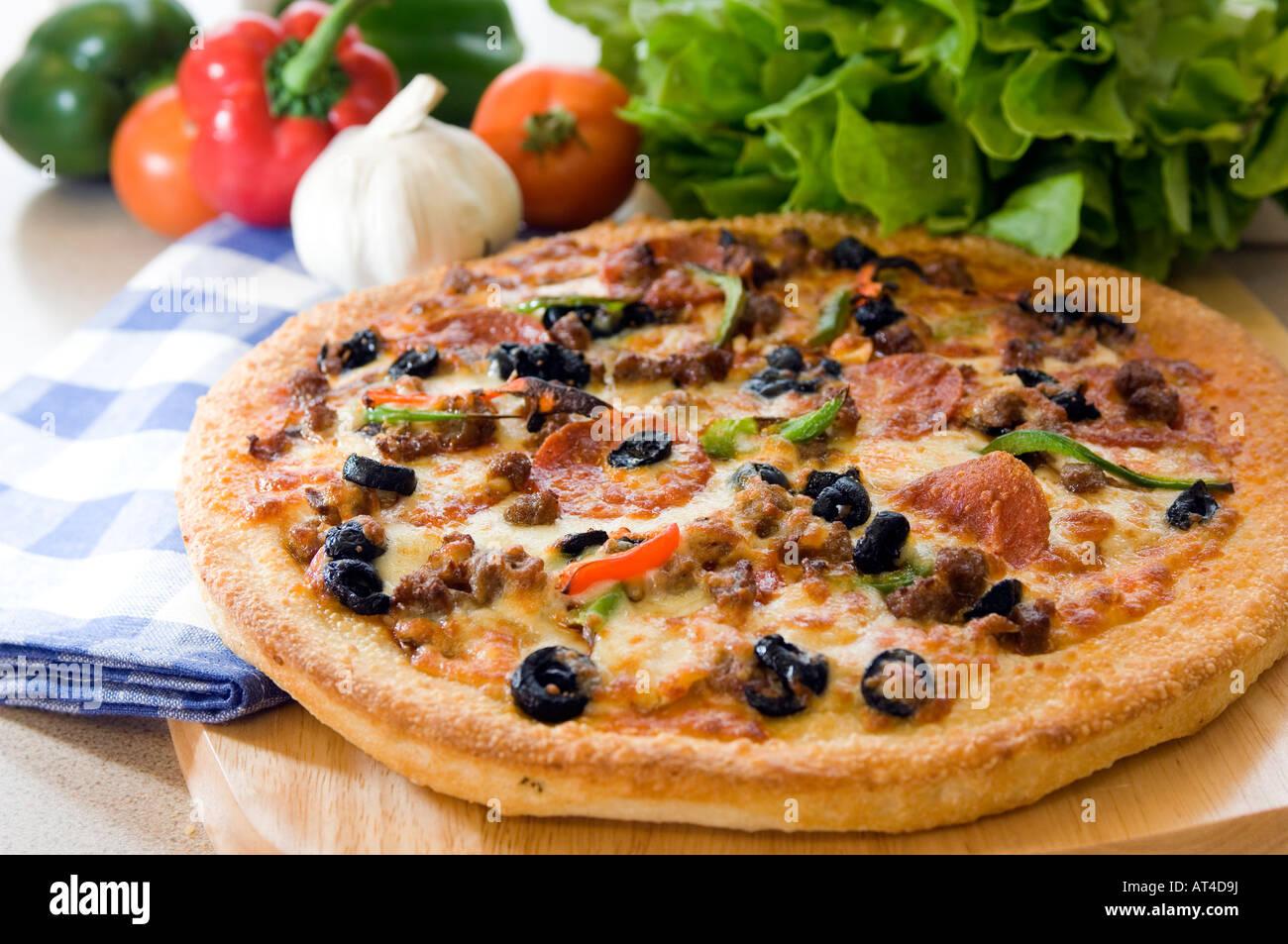 Una calda pizza presentato con prodotti freschi su un tagliere di legno Immagini Stock