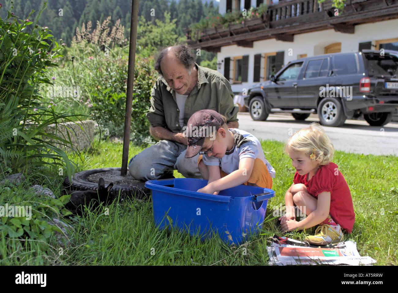 Il nonno e grand bambini che giocano in giardino Immagini Stock