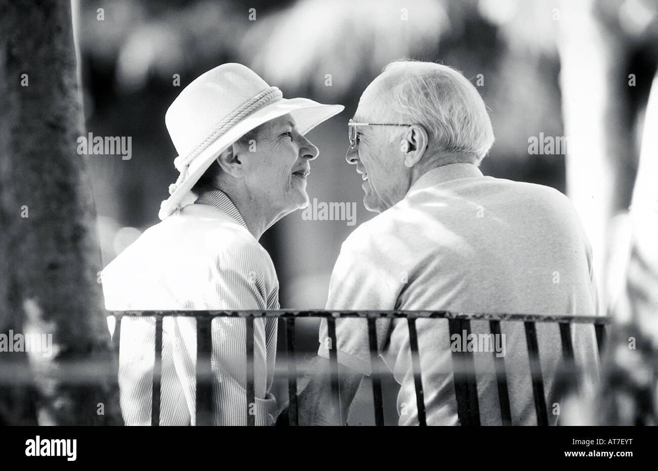 Una coppia matura a parlare intimamente su una panchina nel parco Immagini Stock