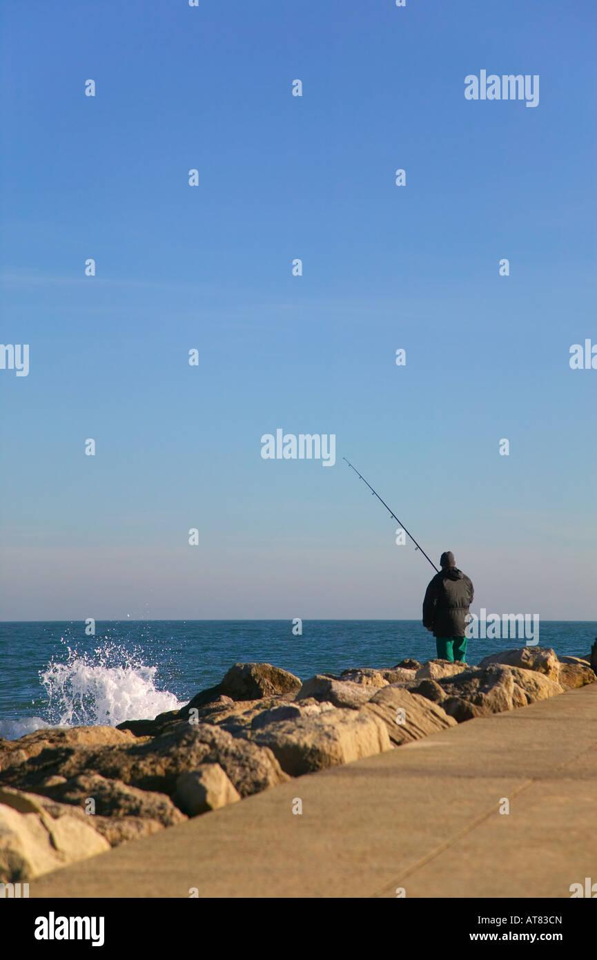 Un pescatore che pesca con lenza da alcune rocce Immagini Stock