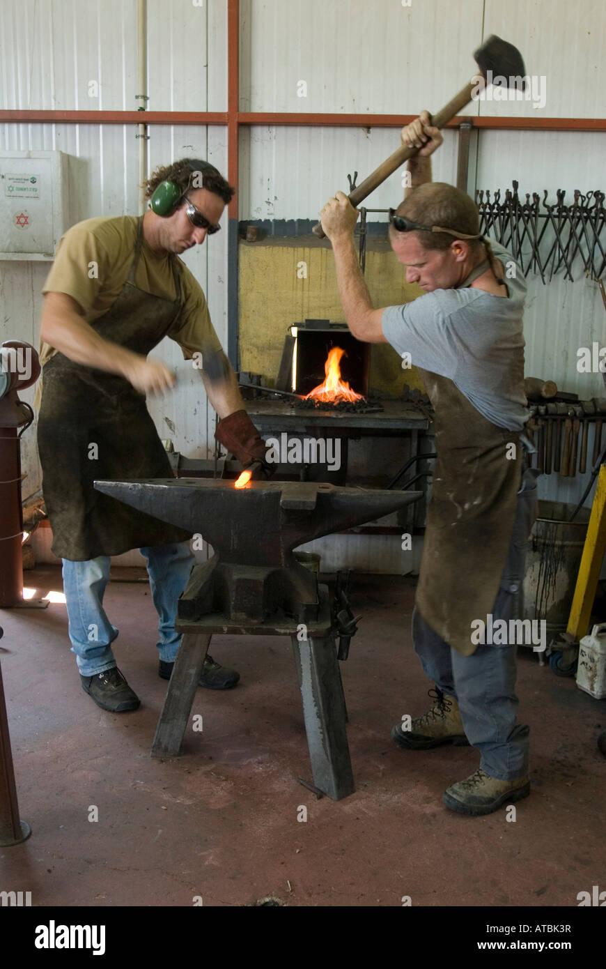 Il vecchio stile fatto a mano i lavoratori del ferro in un piccolo negozio di lavoro vigore sagomando una red hot Immagini Stock
