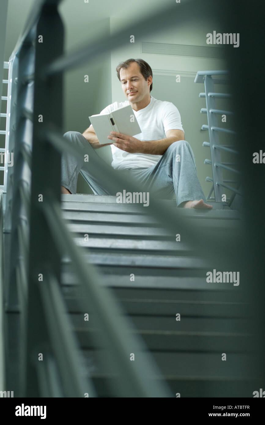 Uomo seduto in cima alla scalinata la lettura di libro, il fuoco selettivo Immagini Stock