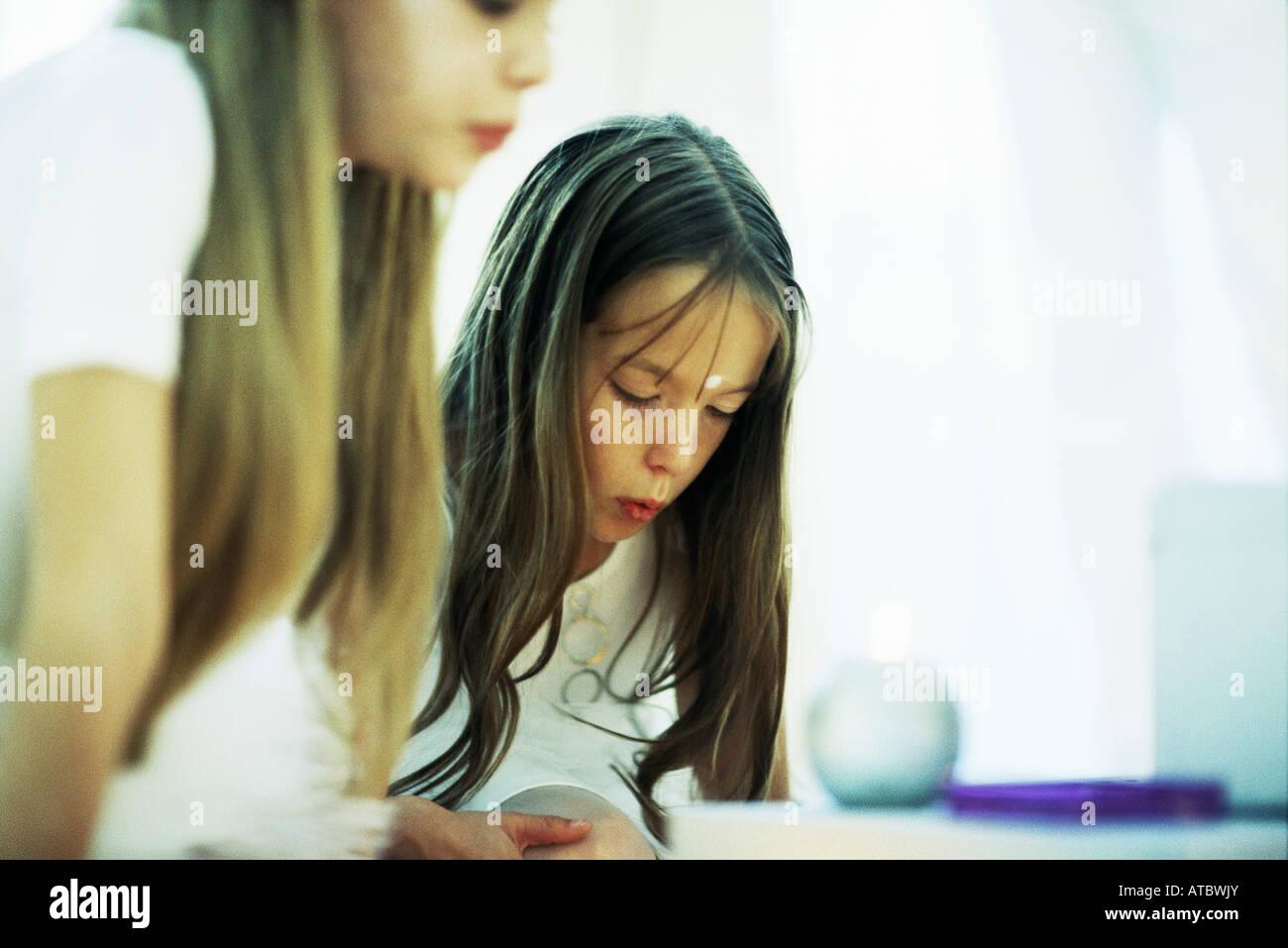 Due ragazze di piegarsi candele, raggrinzimento labbra, vista ritagliata Immagini Stock