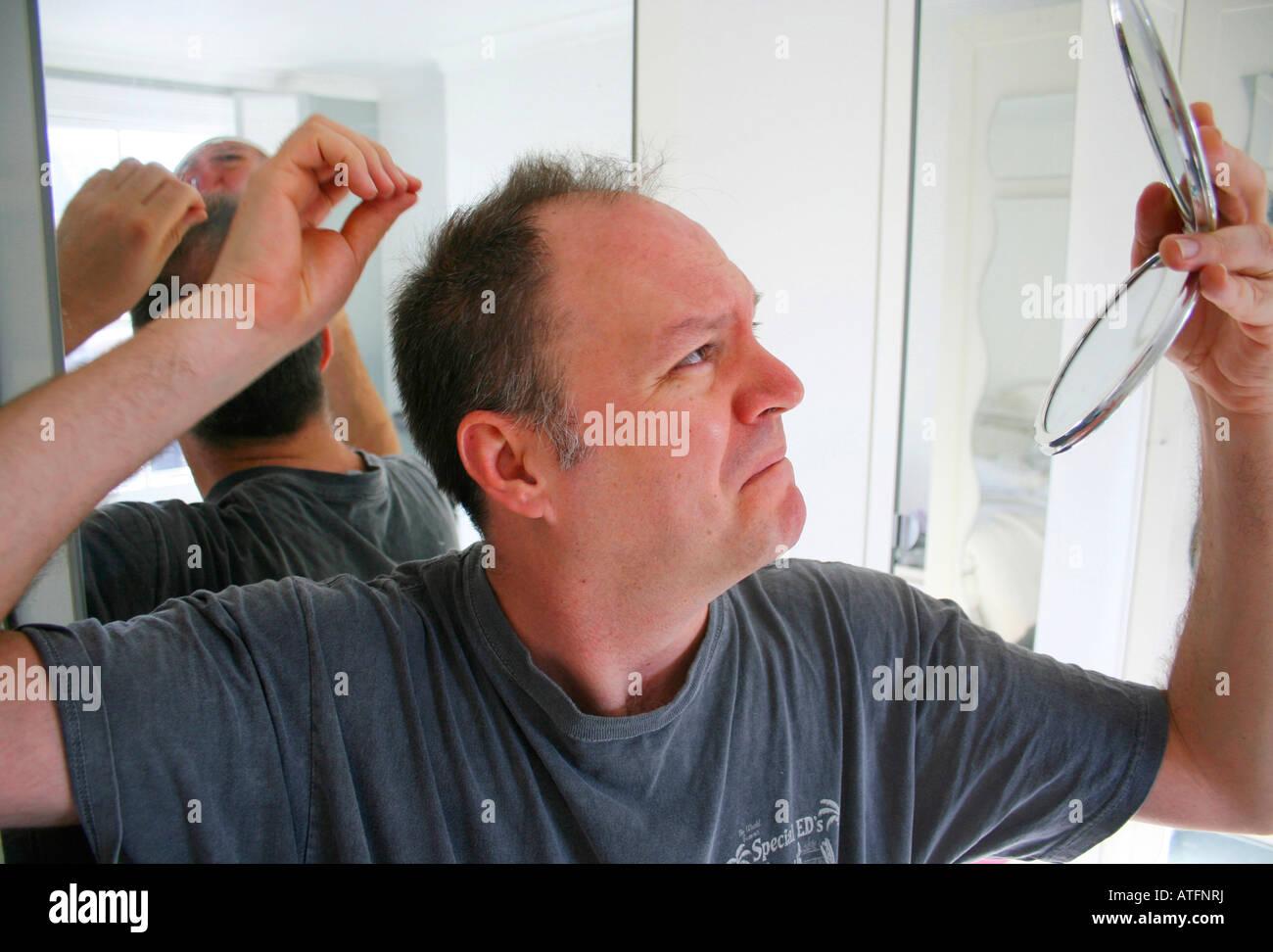 L'uomo controllando il suo assottigliamento dei capelli Immagini Stock