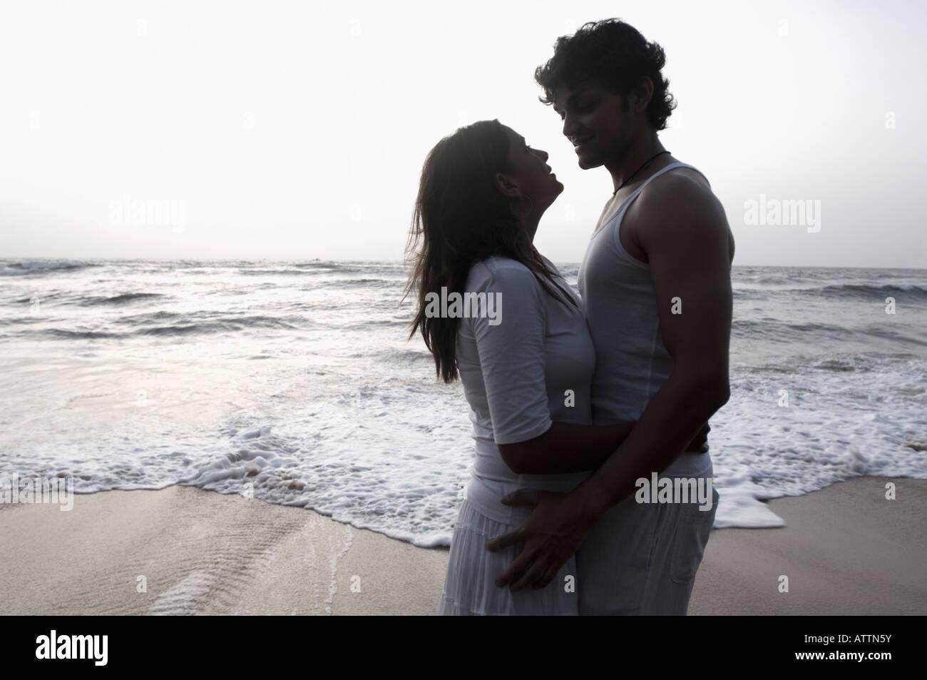 Silhouette di una giovane coppia che abbraccia ogni altro sulla spiaggia, Goa, India Immagini Stock