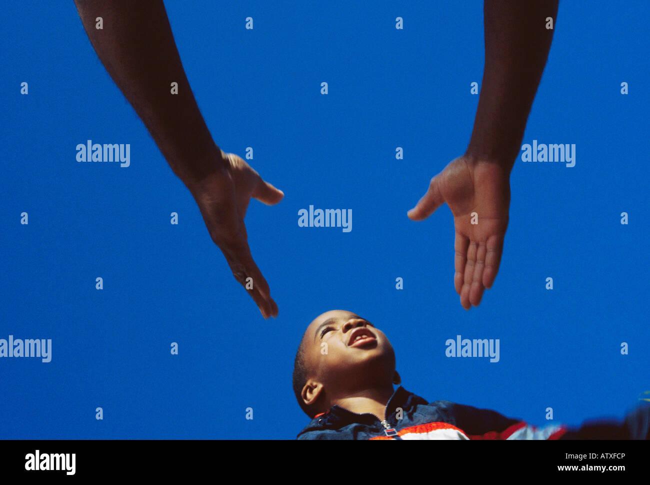 7 anno vecchio African American boy saltando in padre le mani Immagini Stock