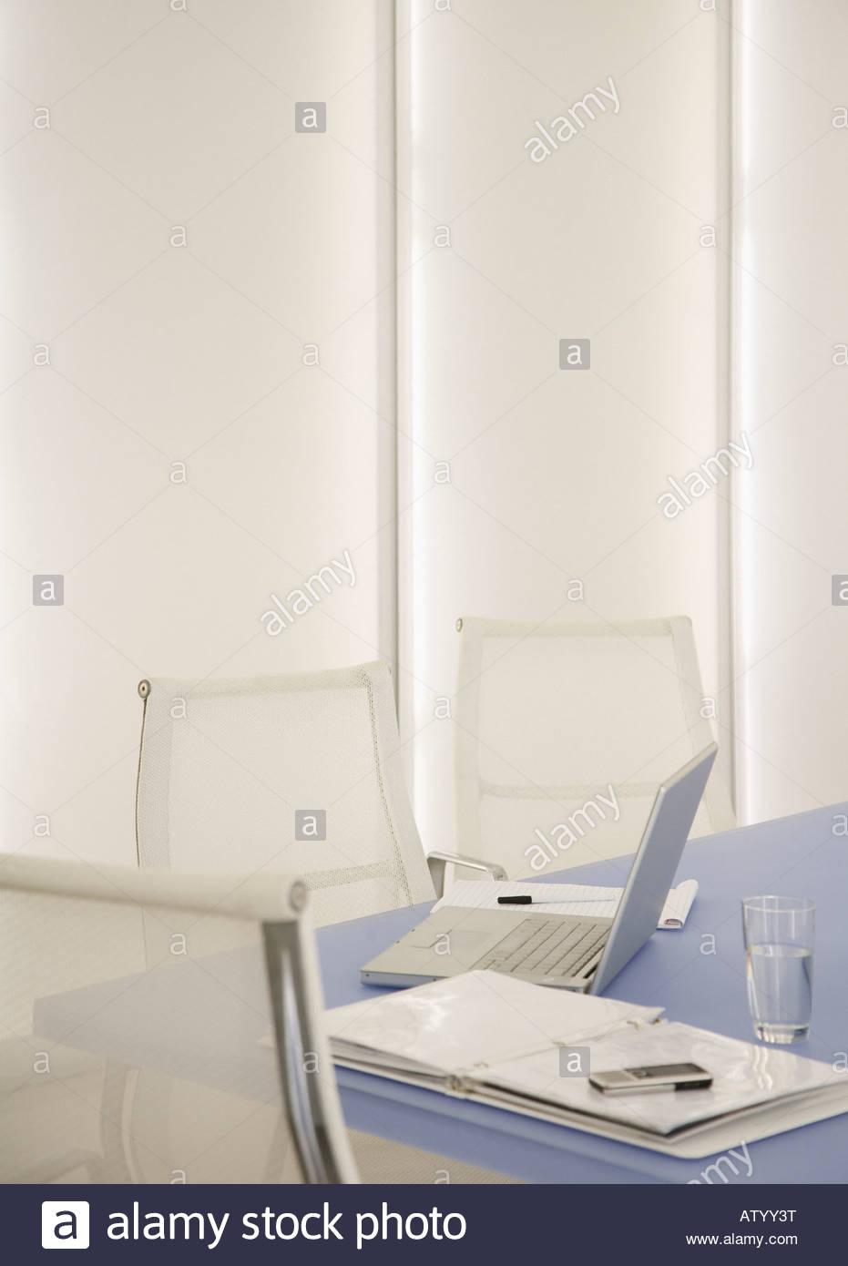 Sala vuota con il laptop e la documentazione sul tavolo Immagini Stock