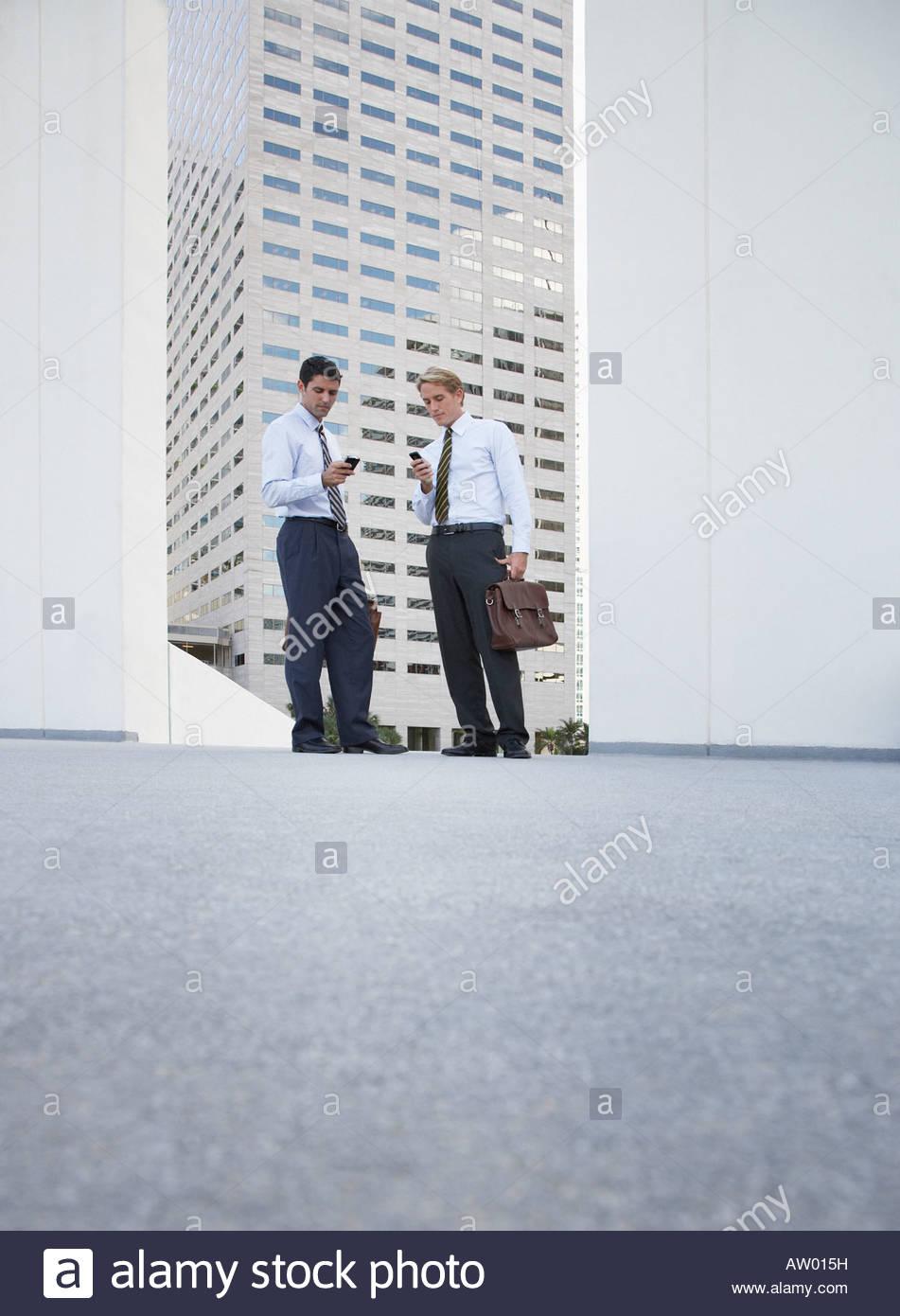 Due proprietari in piedi all'esterno guardando i loro telefoni cellulari Immagini Stock