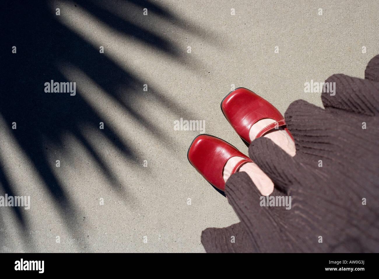Guardando verso il basso in corrispondenza di scarpe rosso rivolto verso l ombra della pianta di Yucca Immagini Stock