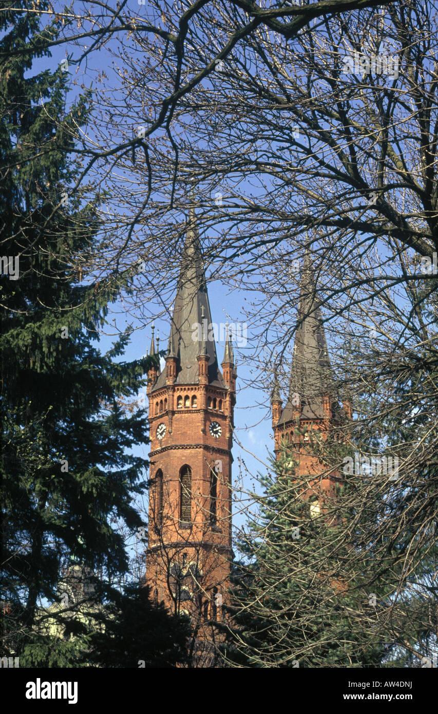Cattedrale Gotica due C xix secolo torri in pietra rossa vista attraverso gli alberi rami spogli Immagini Stock