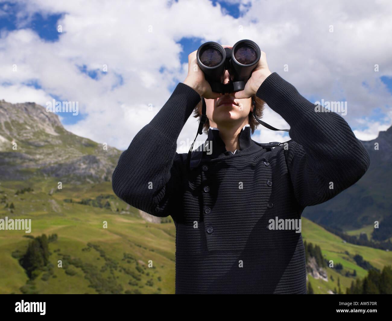 Uomo che guarda attraverso il suo binocolo. Immagini Stock