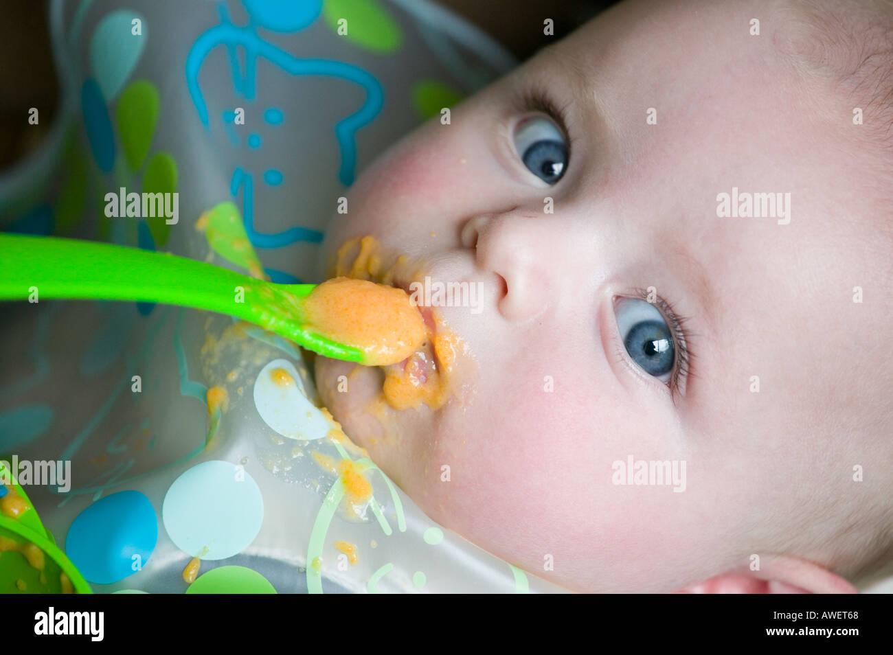 Un mese ffive old baby boy tenta cibo solido per la prima volta Immagini Stock