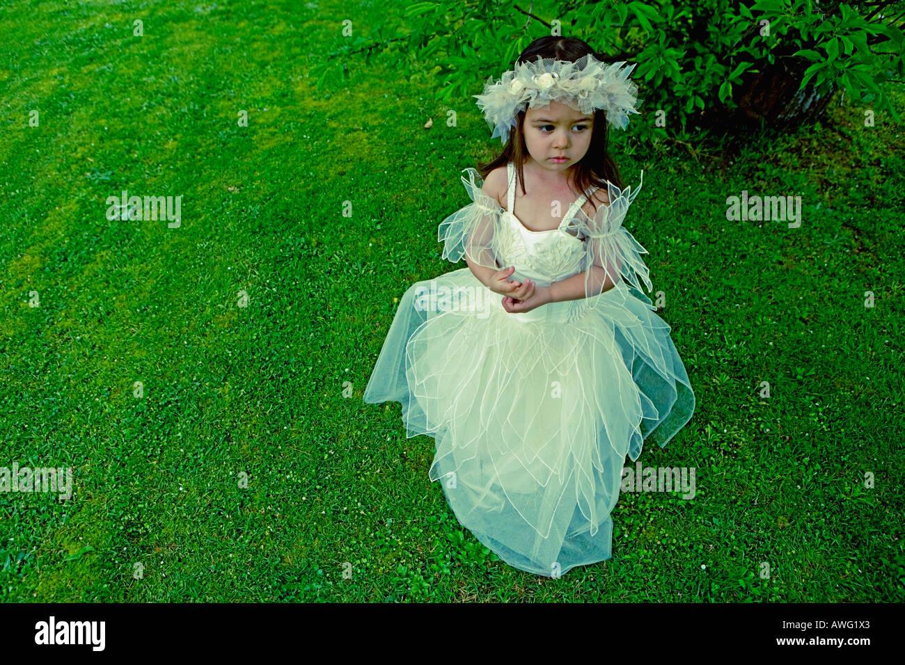 Bambina di 3 anni in una damigella abito sotto un albero su un verde prato Immagini Stock
