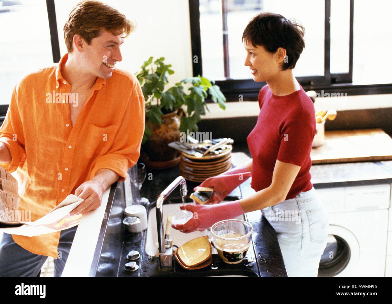 L uomo e la donna in cucina, guardando ogni altro oltre il contatore, donna lavaggio piatti Immagini Stock