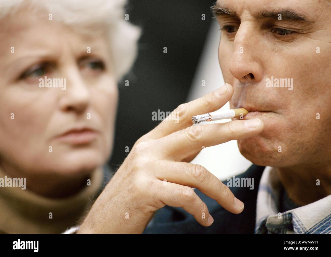 Uomo di fumare, donna sfocati sullo sfondo, close-up Foto Stock