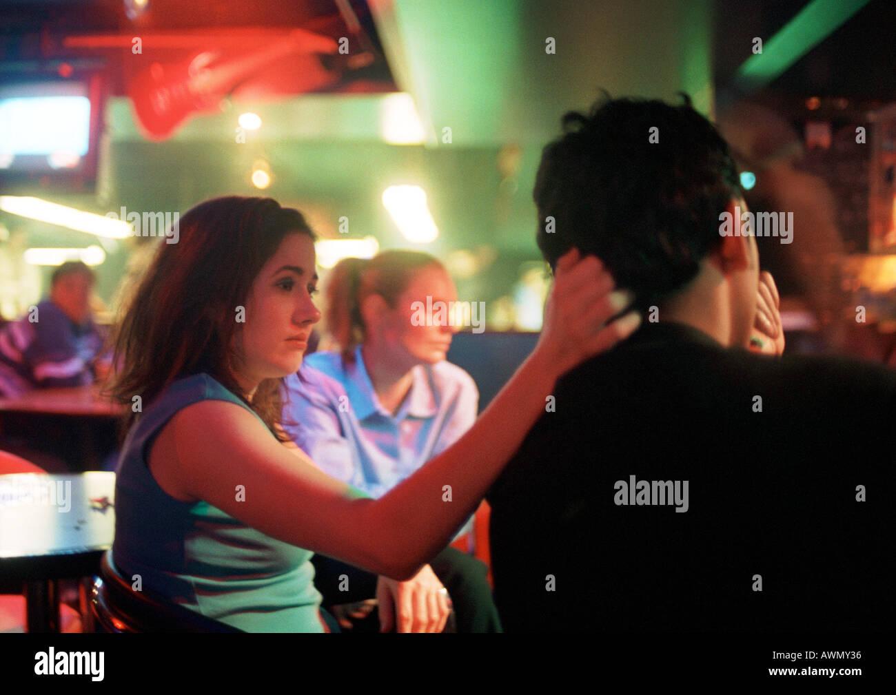 Il giovane e la giovane donna seduta in bar Immagini Stock