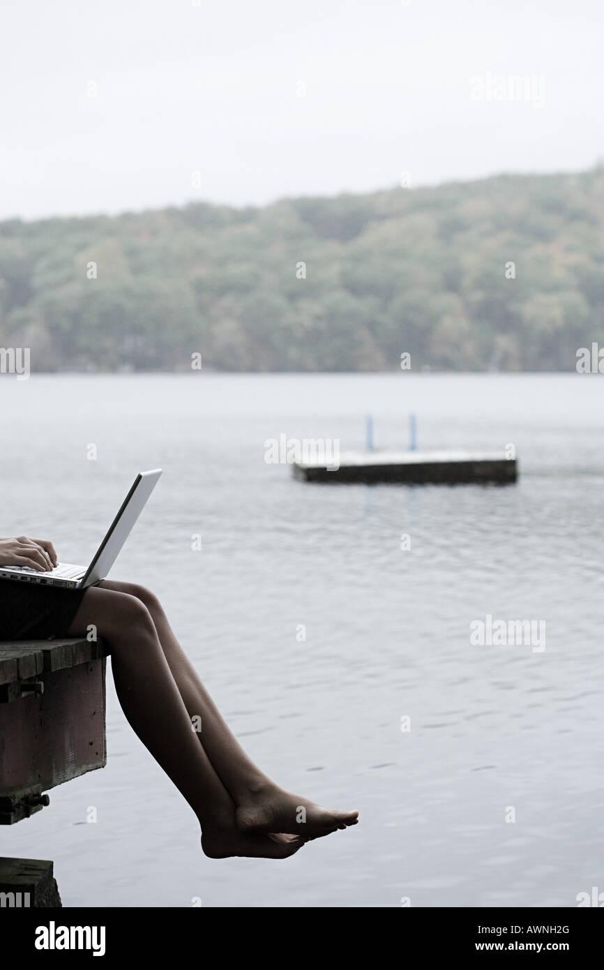 Una donna con un laptop seduto su di un molo Immagini Stock
