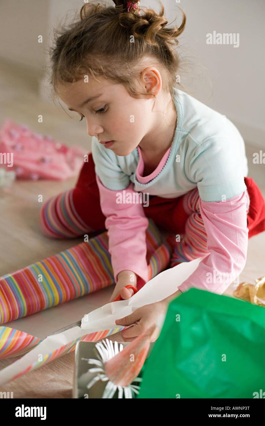 Una ragazza di taglio della carta di avvolgimento Immagini Stock