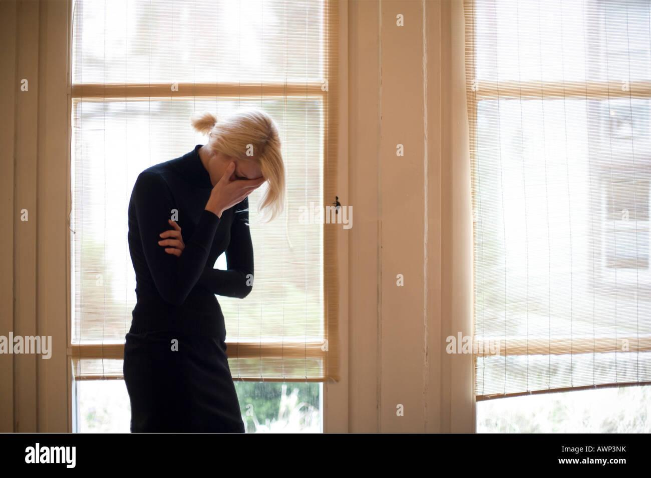 Triste donna bionda in piedi di fronte a grandi finestre Immagini Stock