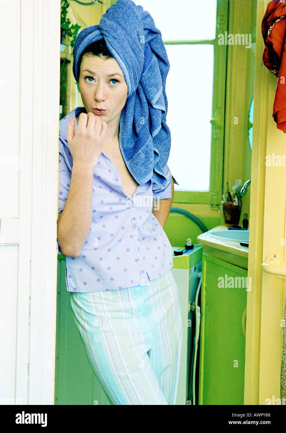 Giovane donna in piedi in bagno, soffiando sul suo dito unghie. Foto Stock