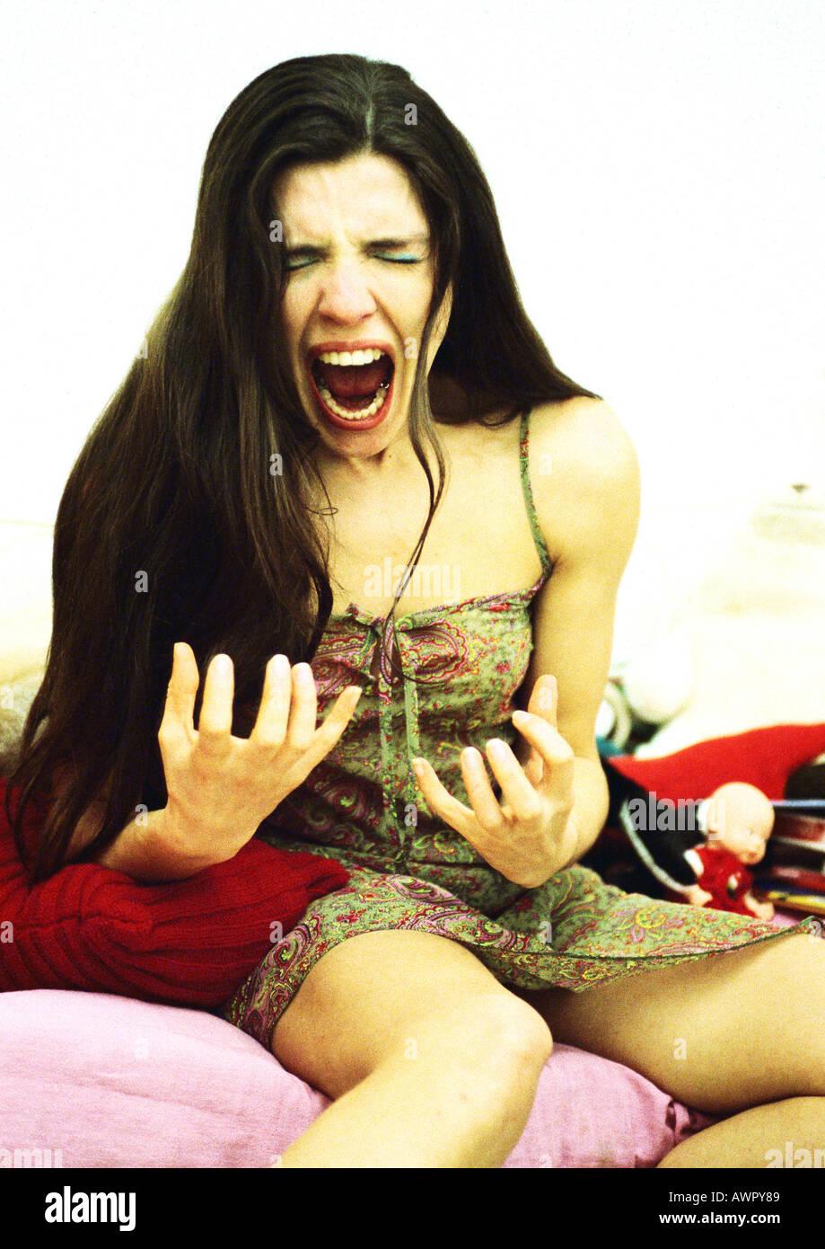 Donna seduta sul letto urlando, ritratto. Foto Stock