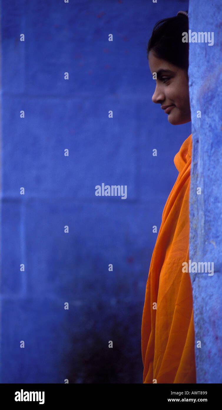 Giovani donne che indossano orange Sari si erge tra pareti blu Jodhpur Rajasthan in India Foto Stock